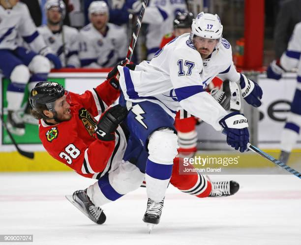 Ryan Hartman of the Chicago Blackhawks falls over the back of Alex Killorn of the Tampa Bay Lightning at the United Center on January 22 2018 in...