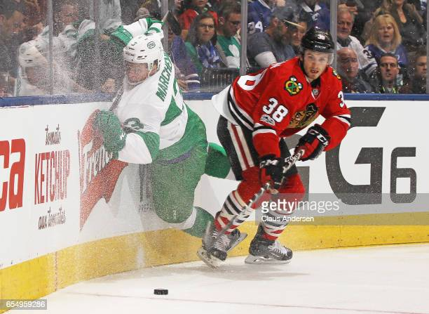 Ryan Hartman of the Chicago Blackhawks slams into Alexey Marchenko of the Toronto Maple Leafs during an NHL game at the Air Canada Centre on March 18...