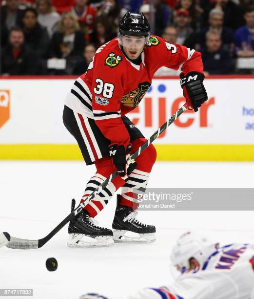 Ryan Hartman of the Chicago Blackhawks takes a pass over Steven Kampfer of the New York Rangers at the United Center on November 15 2017 in Chicago...