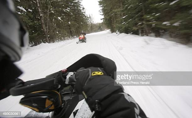 Ryan Harvey of Sanford operates his snowmobile on ITS 84 in Oquossoc on Saturday January 12 2013 Harvey thinks that Maine's law requiring...
