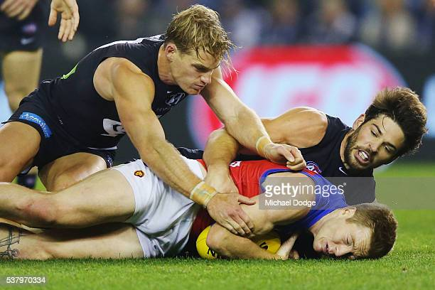 Ryan Harwood of the Lions is tackled by Sam Kerridge of the Blues and Levi Casboult of the Blues during the round 11 AFL match between the Carlton...
