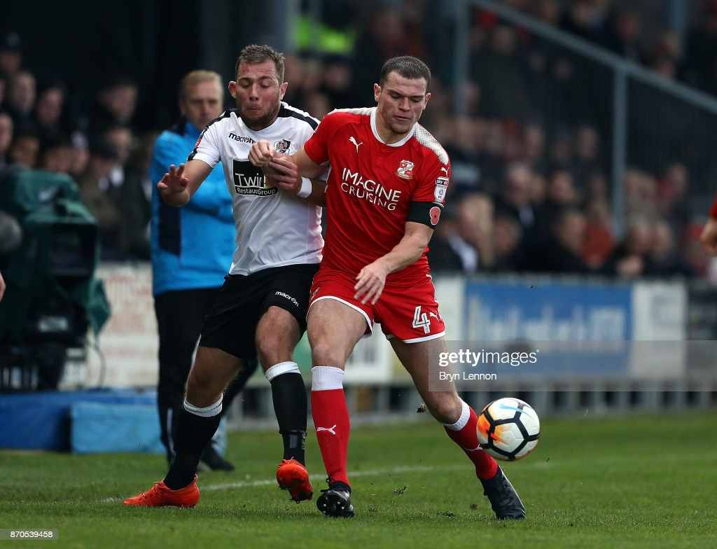Ryan Hayes of Dartford tackles Matty Preston of Swindon Town during The Emirates FA Cup first round match between Dartford and Swindon Town at the Princes Park Stadium on November 5, 2017 in Dartford, England.