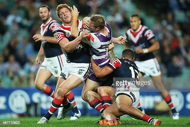 Ryan Hinchcliffe of the Storm is tackled by Dylan Napa and Sio Siua Taukeiaho of the Roosters during the NRL qualifying final match between the...