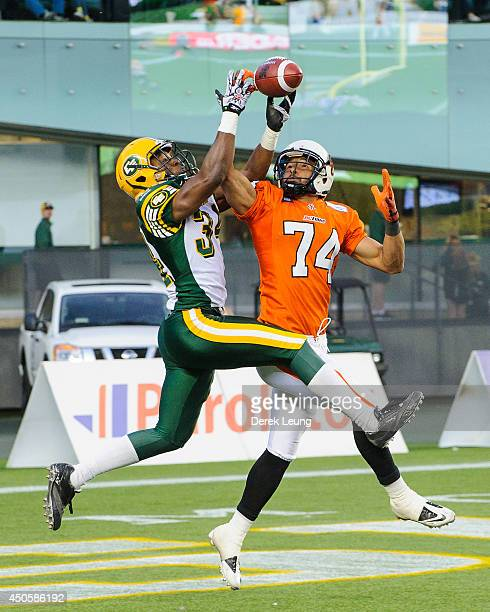 Ryan Hinds of the Edmonton Eskimos beats Brian Burnham of the BC Lions to the ball during a CFL game at Commonwealth Stadium on June 13 2014 in...