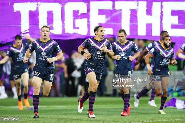 Ryan Hoffman Billy Slater and Cameron Smith run through the banner during the round three NRL match between the Melbourne Storm and the North...