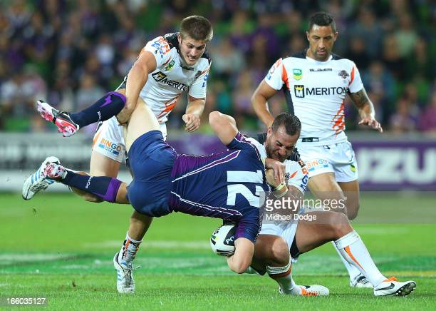 Ryan Hoffman of the Storm gets tackled by Blake Ayshford and Bodene Thompson of the Tigers during the round 5 NRL match between the Melbourne Storm...