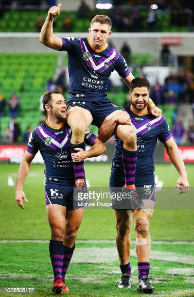 Ryan Hoffman of the Storm is carried off by Cameron Smith and Jesse Browmwich of the Storm after his last home and away match during the round 25 NRL...