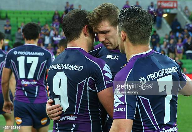 Ryan Hoffman of the Storm is consoled by Cameron Smith and Cooper Cronk after playing his last game for the Storm during the NRL 2nd Elimination...
