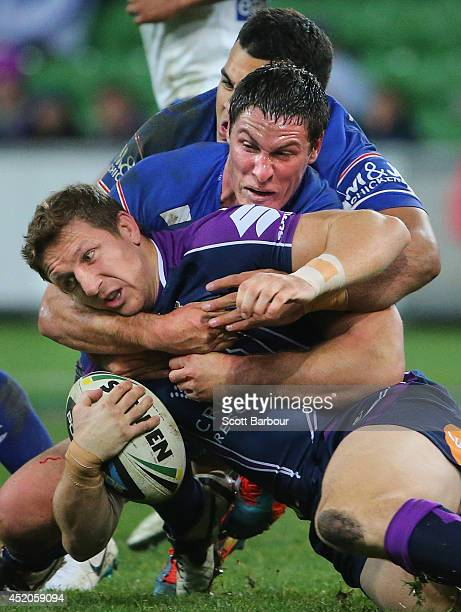Ryan Hoffman of the Storm is tackled during the round 18 NRL match between the Melbourne Storm and the Canterbury Bulldogs at AAMI Park on July 12...
