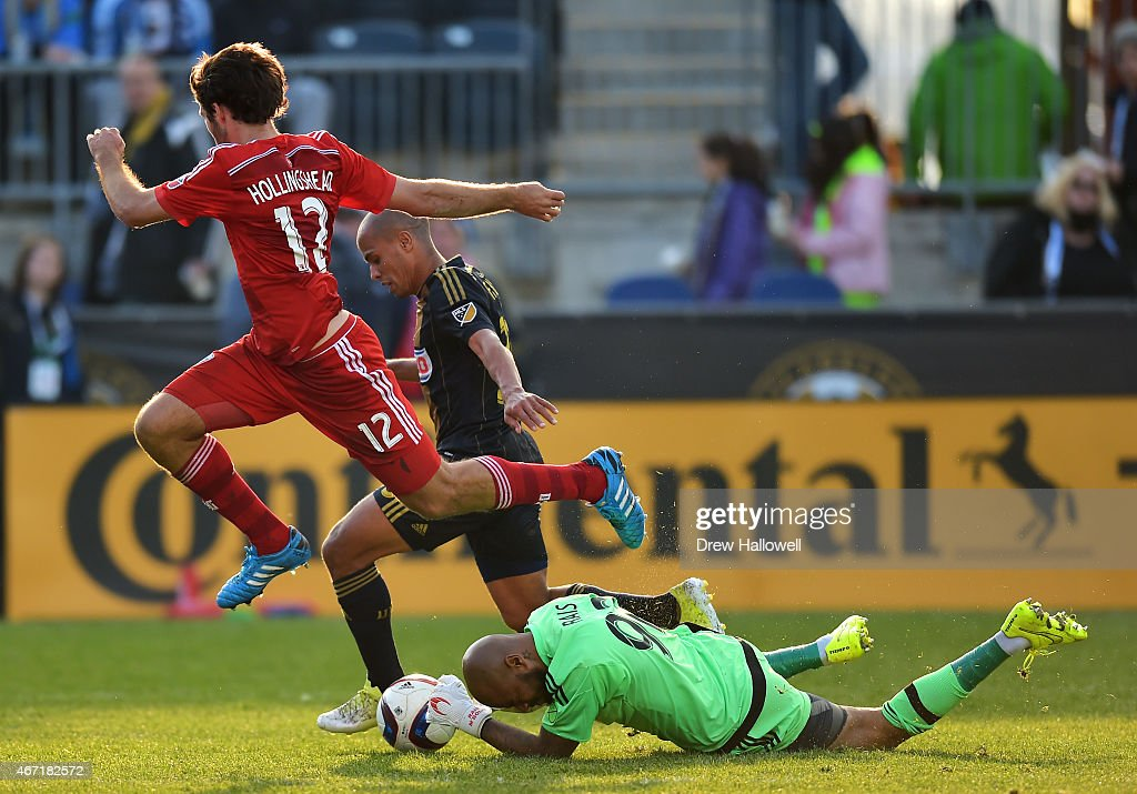 Ryan Hollingshead #12 of FC Dallas jumps over Rais Mbolhi #92 of Philadelphia Union as he makes a save and teammate Fabinho #33 tries to defend at PPL Park on March 21, 2015 in Chester, Pennsylvania. Dallas won 2-0.