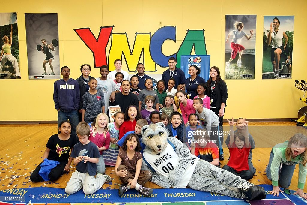 Ryan Hollins, mascot Crunch and broadcaster Alan Horton of the Minnesota Timberwolves poses for a photo with a group of kids as they host a Reading Time-out at the Midway YMCA on March 29, 2010 in St. Paul, Minnesota.