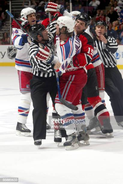 Ryan Hollweg of the New York Rangers gets held back by Jamie Langenbrunner of the New Jersey Devils and linesman Angelo D'Amico during a shoving...