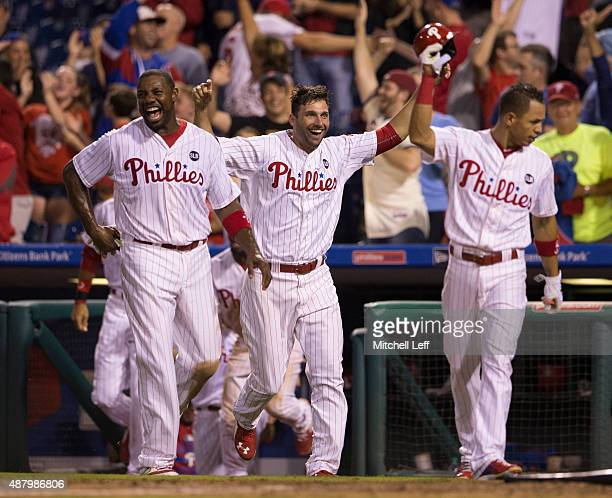 Ryan Howard Jeff Francoeur and Cesar Hernandez of the Philadelphia Phillies celebrate after the walkoff tworun home run hit by Cody Asche in the...