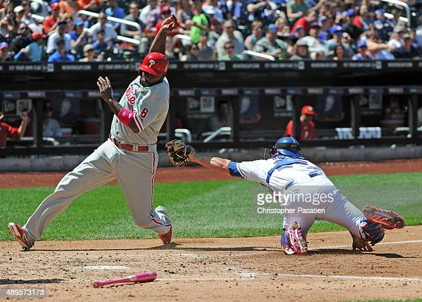 Ryan Howard of the Philadelphia Phillies avoids the tag attempt of Anthony Recker of the New York Mets to score a run during the top of the fourth...