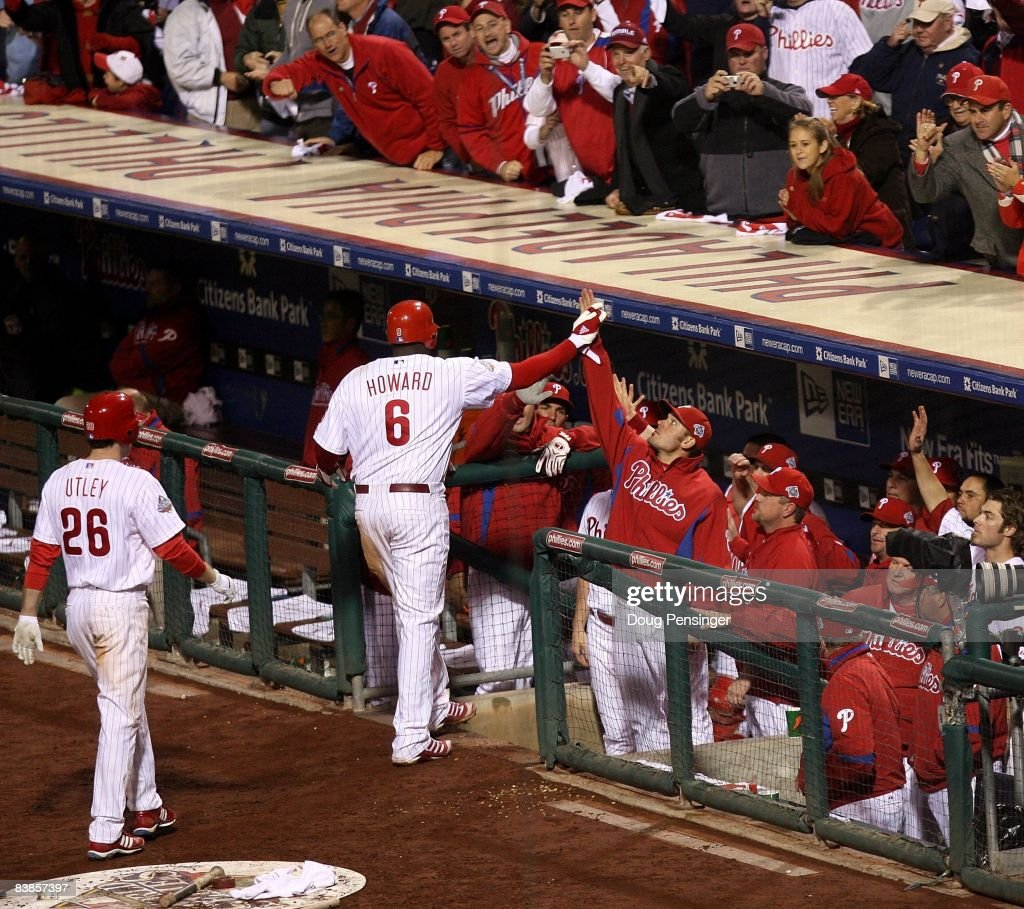 Ryan Howard #6 of the Philadelphia Phillies celebrates with teammates in the dugout after he hit a 2-run home run which also scored Chase Utley #26 in the bottom of the eighth inning against the Tampa Bay Rays looks on during game four of the 2008 MLB World Series on October 26, 2008 at Citizens Bank Park in Philadelphia, Pennsylvania.