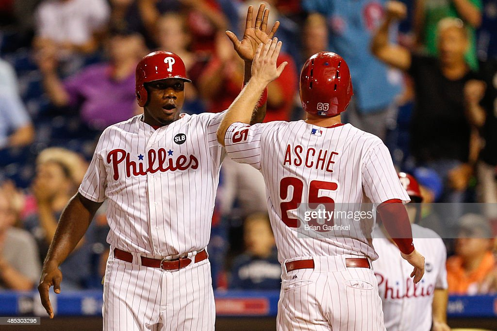 Ryan Howard #6 of the Philadelphia Phillies high-fives Cody Asche #25 after both scored on a Cameron Rupp double in the eighth inning of the game against the New York Mets at Citizens Bank Park on August 26, 2015 in Philadelphia, Pennsylvania. The Mets won 9-4.