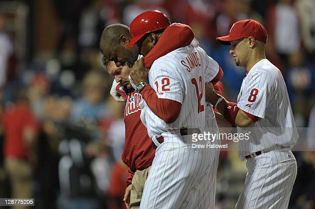Ryan Howard of the Philadelphia Phillies is assisted off of the field after he was hurt on the last play of the game as the Phillies lost 1-0 against...