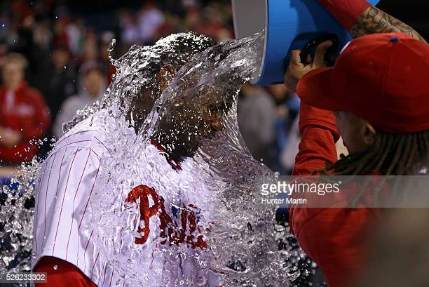 Ryan Howard of the Philadelphia Phillies is doused with water by Emmanuel Burriss after hitting a game winning solo home run in the 11th inning...
