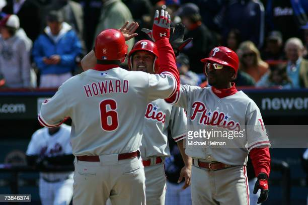 Ryan Howard of the Philadelphia Phillies is greeted at home by Shane Victorino and Jimmy Rollins after his threerun homer in the sixth inning against...