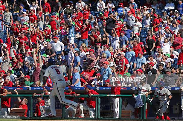Ryan Howard of the Philadelphia Phillies runs after hitting a deep fly ball as the fans react in the ninth inning during a game against the...