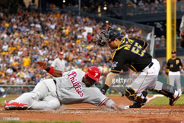 Ryan Howard of the Philadelphia Phillies scores on a play at the plate against Russell Martin of the Pittsburgh Pirates in the sixth inning during...