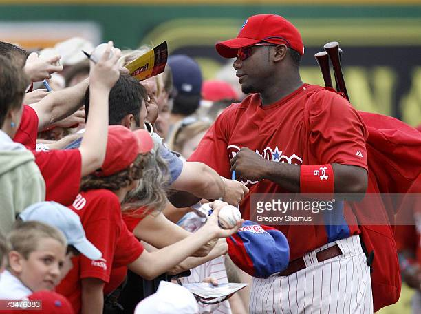Ryan Howard of the Philadelphia Phillies signs autographs at the first base line after leaving a game against the Cleveland Indians during a Spring...