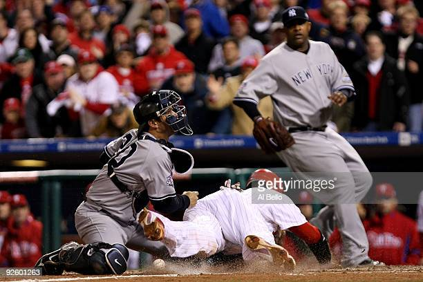 Ryan Howard of the Philadelphia Phillies slides safely into home to score against catcher Jorge Posada of the New York Yankees on a RBI single by...
