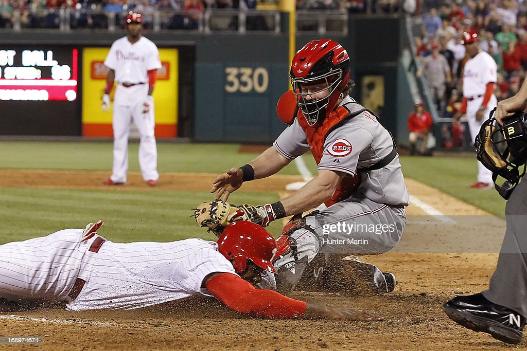 Ryan Howard #6 of the Philadelphia Phillies slides under the tag of Ryan Hanigan #29 at home plate for a run against the Cincinnati Reds at Citizens Bank Park on May 17, 2013 in Philadelphia, Pennsylvania. The Phillies won 5-3.