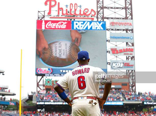 Ryan Howard of the Philadelphia Phillies watches the video board as his son Darian places a plaque commemorating the landing spot of his franchise...