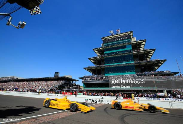 Ryan HunterReay driver of the Andretti Autosport DHL Honda drosses the finish line ahead of Helio CastroNeves driver of the Penzoil Ultra Platinum...