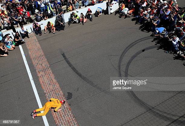 Ryan HunterReay driver of the Andretti Autosport DHL Honda kisses the bricks at the finish line after winning the 98th running of the Indianapolis...