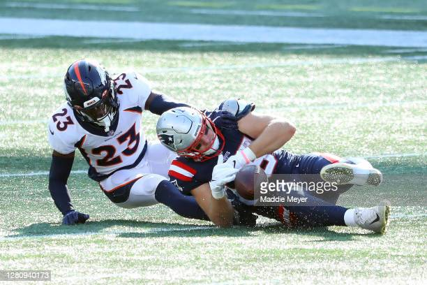 Ryan Izzo of the New England Patriots drops a pass against Michael Ojemudia of the Denver Broncos during the second half at Gillette Stadium on...