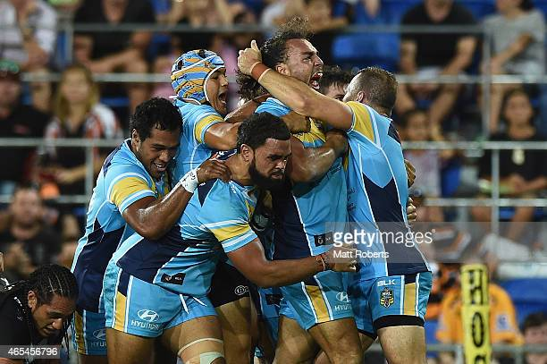 Ryan James of the Titans celebrates scoring a try with team mates during the round one NRL match between the Gold Coast Titans and the Wests Tigers...