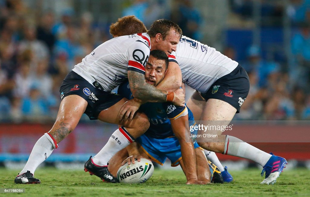 Ryan James of the Titans is tackled by Jake Friend of the Roosters during the round one NRL match between the Gold Coast Titans and the Sydney Roosters at Cbus Super Stadium on March 4, 2017 in Gold Coast, Australia.