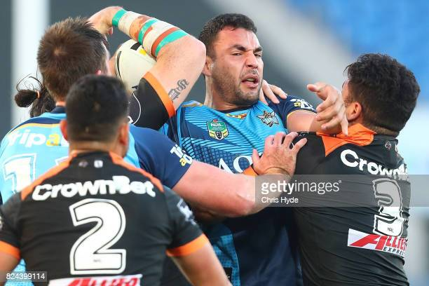 Ryan James of the Titans is tackled during the round 21 NRL match between the Gold Coast Titans and the Wests Tigers at Cbus Super Stadium on July 30...