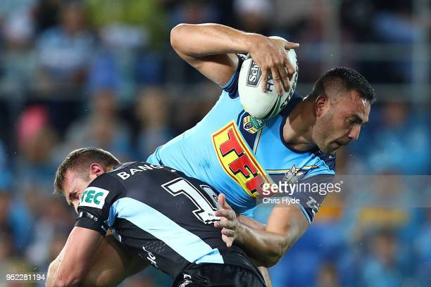 Ryan James of the Titans is tackled during the round eight NRL match between the Gold Coast Titans and Cronulla Sharks at Cbus Super Stadium on April...