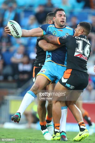 Ryan James of the Titans offloads while tackled during the round 21 NRL match between the Gold Coast Titans and the Wests Tigers at Cbus Super...