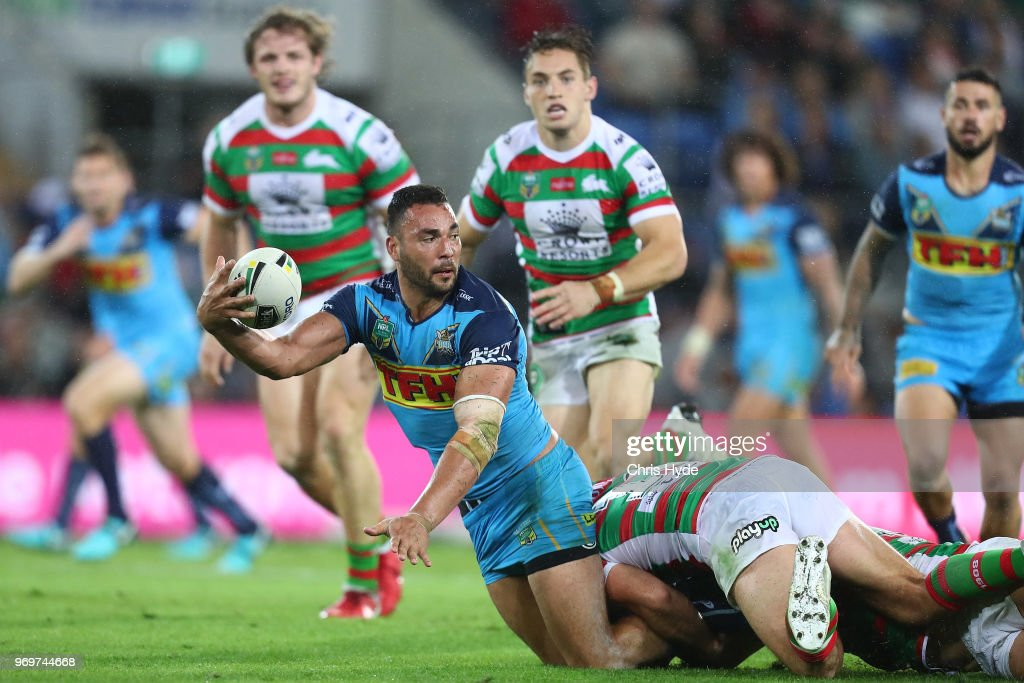 Ryan James of the Titans passes while tackled during the round 14 NRL match between the Gold Coast Titans and the South Sydney Rabbitohs at Cbus Super Stadium on June 8, 2018 in Gold Coast, Australia.