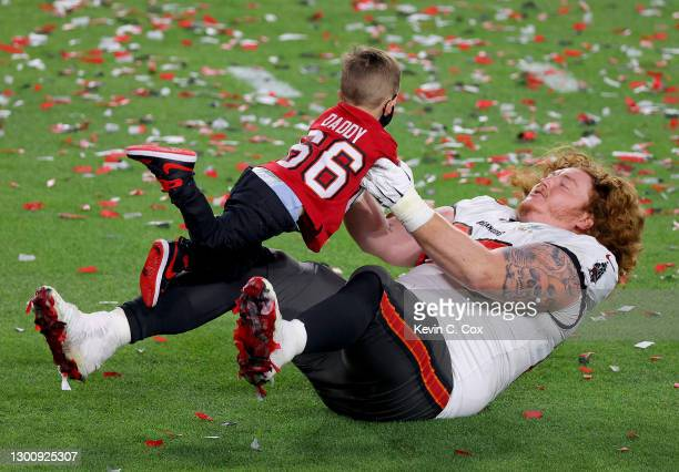 Ryan Jensen of the Tampa Bay Buccaneers celebrates with his child after defeating the Kansas City Chiefs in Super Bowl LV at Raymond James Stadium on...