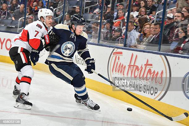 Ryan Johansen of the Columbus Blue Jackets holds off Kyle Turris of the Ottawa Senators as he skates after a loose puck during the first period on...