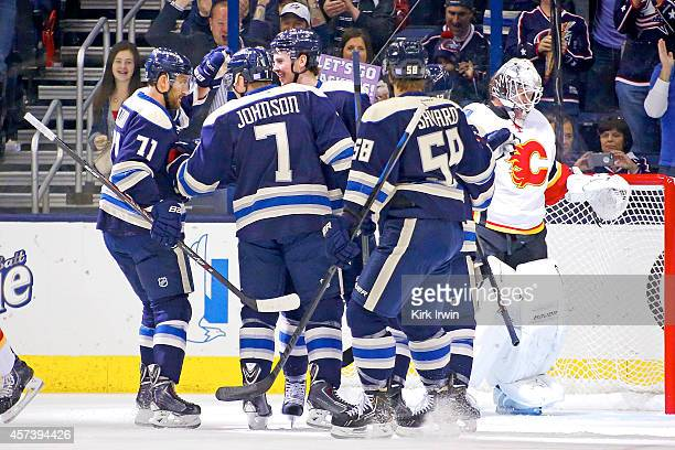 Ryan Johansen of the Columbus Blue Jackets is congratulated by his teammates after beating Karri Ramo of the Calgary Flames for a power play goal...