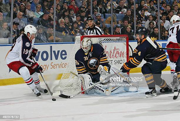 Ryan Johansen of the Columbus Blue Jackets is defended by Chad Johnson and Josh Gorges of the Buffalo Sabres as he comes from behind the net on...