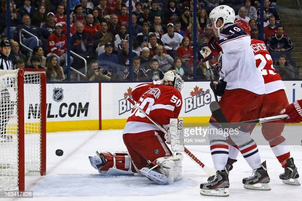 Ryan Johansen of the Columbus Blue Jackets watches as Jonas Gustavsson of the Detroit Red Wings is unable to stop a shot from Jack Johnson of the...