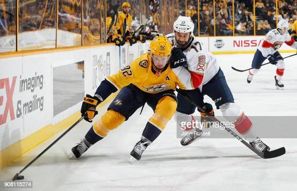Ryan Johansen of the Nashville Predators protects the puck against Derek MacKenzie of the Florida Panthers during an NHL game at Bridgestone Arena on...