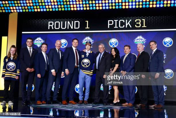 Ryan Johnson, 31st overall pick of the Buffalo Sabres, poses for a photo onstage with team personnel during the first round of the 2019 NHL Draft at...