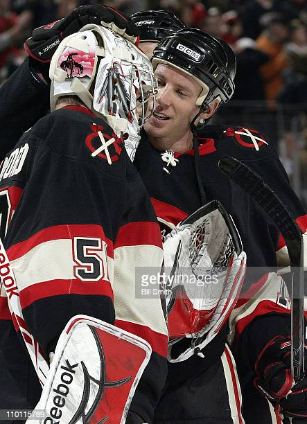 Ryan Johnson of the Chicago Blackhawks celebrates with team goalie Corey Crawford after defeating the Carolina Hurricanes on March 4 2011 at the...
