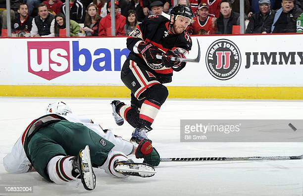 Ryan Johnson of the Chicago Blackhawks shoots the puck over fallen Clayton Stoner of the Minnesota Wild on January 25 2011 at the United Center in...