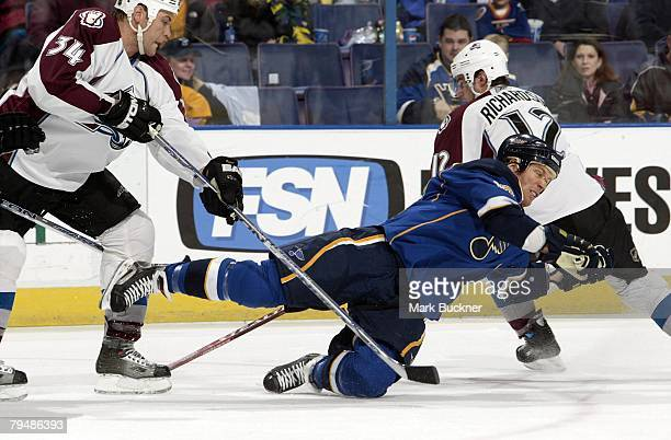 Ryan Johnson of the St Louis Blues falls while skating against Kurt Sauer of the Colorado Avalanche and Brad Richardson of the Colorado Avalanche at...