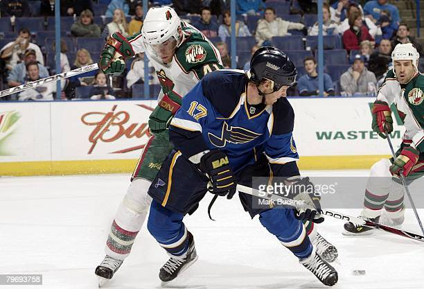 Ryan Johnson of the St Louis Blues looks for the puck as he gets tangled with Martin Skoula of the Minnesota Wild at Scottrade Center February 10...