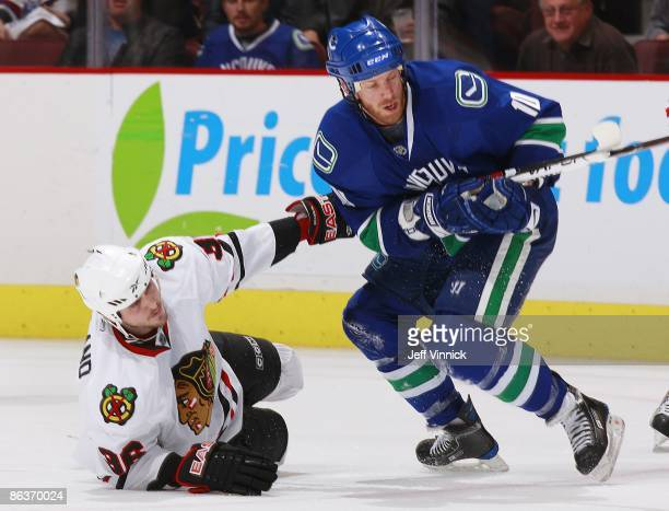 Ryan Johnson of the Vancouver Canucks and Dave Bolland of the Chicago Blackhawks get tangled up during Game Two of the Western Conference Semifinal...